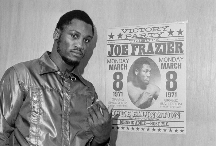 "FILE - Heavyweight champ Joe Frazier poses by a poster advertising his ""victory party"" as he leaves his dressing room after a final public workout in Philadelphia ahead of his title defense fight against Muhammad Ali in New York on March 8, in this March 6, 1971, file photo. Their first fight at Madison Square Garden was so epic it was billed as the Fight of the Century, and 50 years later it reigns undefeated. (AP Photo/Bill Ingraham, File)"