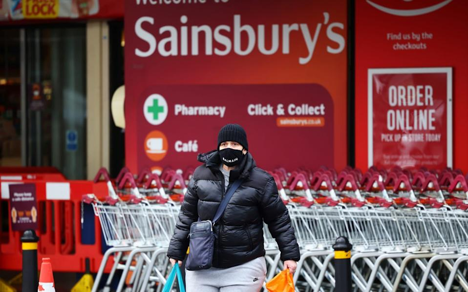 A person wearing a face mask leaves a Sainsbury's supermarket - Henry Nicholls/REUTERS