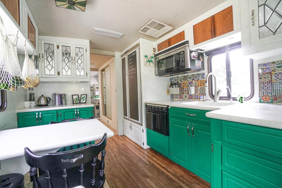 the renovated kitchen with green cabinetry in walker family RV