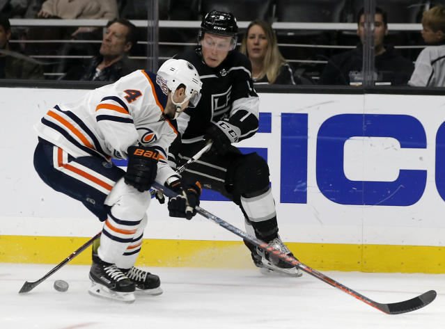 Los Angeles Kings defenseman Paul LaDue, right, controls the puck against Edmonton Oilers defenseman Kris Russell, left, during the second period of an NHL hockey game in Los Angeles, Sunday, Nov. 25, 2018. (AP Photo/Alex Gallardo)