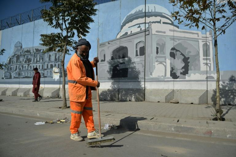 An Afghan worker cleans a road next to a mural in Kabul (AFP/HOSHANG HASHIMI)