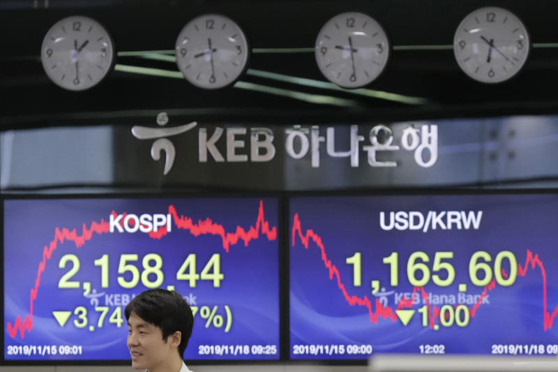 A currency trader walks near screens showing the Korea Composite Stock Price Index (KOSPI), left, and the foreign exchange rate between U.S. dollar and South Korean won, right, at the foreign exchange dealing room in Seoul, South Korea, Monday, Nov. 18, 2019. Asian shares are mixed Monday in a cautious mode after Wall Street closed out the week with milestones as the Dow Jones Industrial Average crossed 28,000 for the first time and the S&P 500 and Nasdaq hit record highs. (AP Photo/Lee Jin-man)
