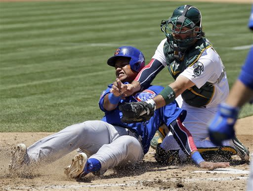 Chicago Cubs' Starlin Castro, left, is tagged out at the plate by Oakland Athletics catcher Derek Norris while trying to score from second base on a single by Alfonso Soriano during the fourth inning of a baseball game on Thursday, July 4, 2013, in Oakland, Calif. (AP Photo/Marcio Jose Sanchez)