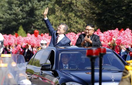 South Korean President Moon Jae-in and North Korean leader Kim Jong Un react during a car parade in Pyongyang, North Korea, September 18, 2018. Pyeongyang Press Corps/Pool via REUTERS