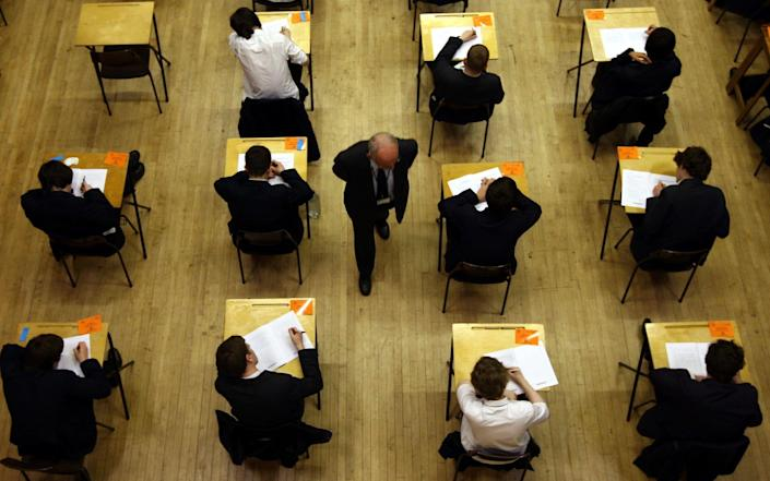 Pupils taking an exam, watched over by an invigilator - David Jones/PA