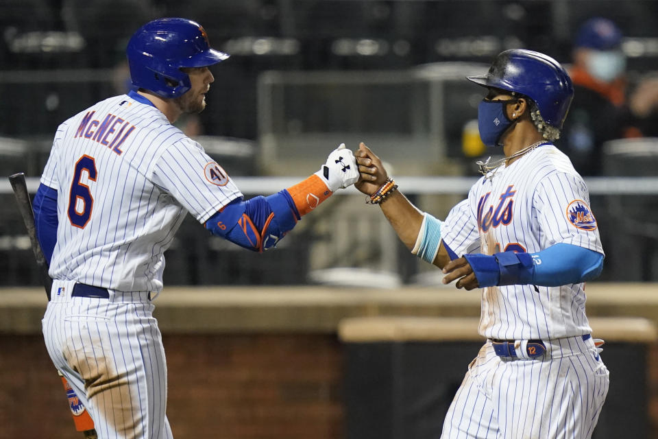 New York Mets' Jeff McNeil, left, fist bumps Francisco Lindor after Lindor scored on a sacrifice fly ball by Pete Alonso during the seventh inning of a baseball game Wednesday, April 14, 2021, in New York. (AP Photo/Frank Franklin II)