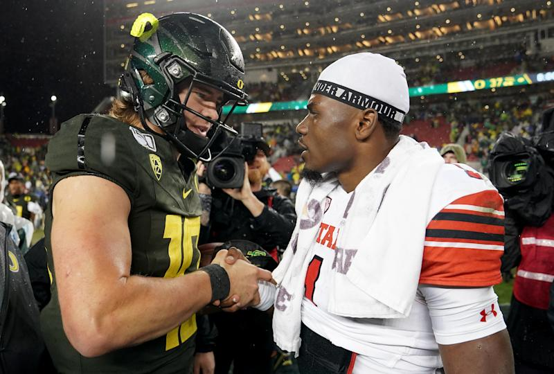 Justin Herbert #10 of the Oregon Ducks shakes hands with quarterback Tyler Huntley #1 of the Utah Utes after the Ducks defeated the Utes 37-15 in the Pac-12 title game. (Thearon W. Henderson/Getty Images)