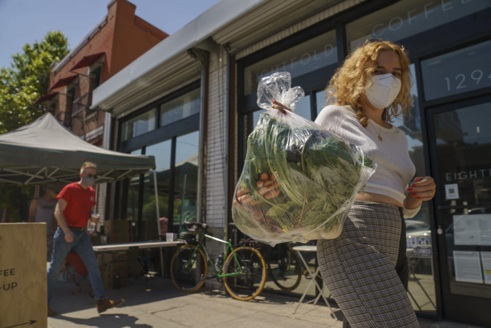 Fashion designer Josie Vand wears a facemask as she retrieves a bag with organic vegetables from a farm box from County Line Harvest in Los Angeles on Friday, April 2, 2021. California has been easing COVID-19 restrictions as it recovers from a deadly winter surge, although public health officials still urge people to follow social distancing and mask-wearing protocols. Rates of hospitalizations and deaths have plunged, and the rate of people testing positive for the virus is at a near-record low. (AP Photo/Damian Dovarganes)