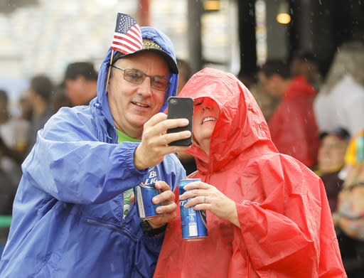 Race fans make a selfie photo in the Fan Zone during a rain shower before the NASCAR Sprint cup Series auto race at Daytona International Speedway in Daytona Beach, Fla., Saturday, July 5, 2014. (AP Photo/Terry Renna)