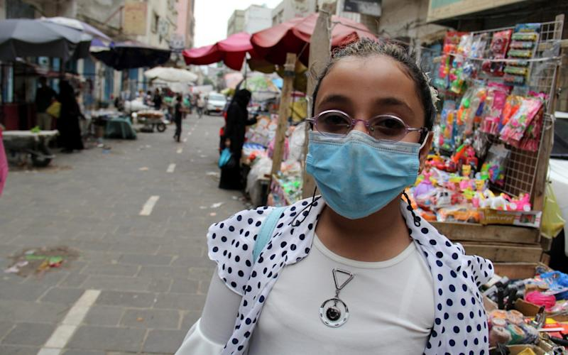 A girl wearing a protective face mask is pictured at a market in Taiz - Reuters