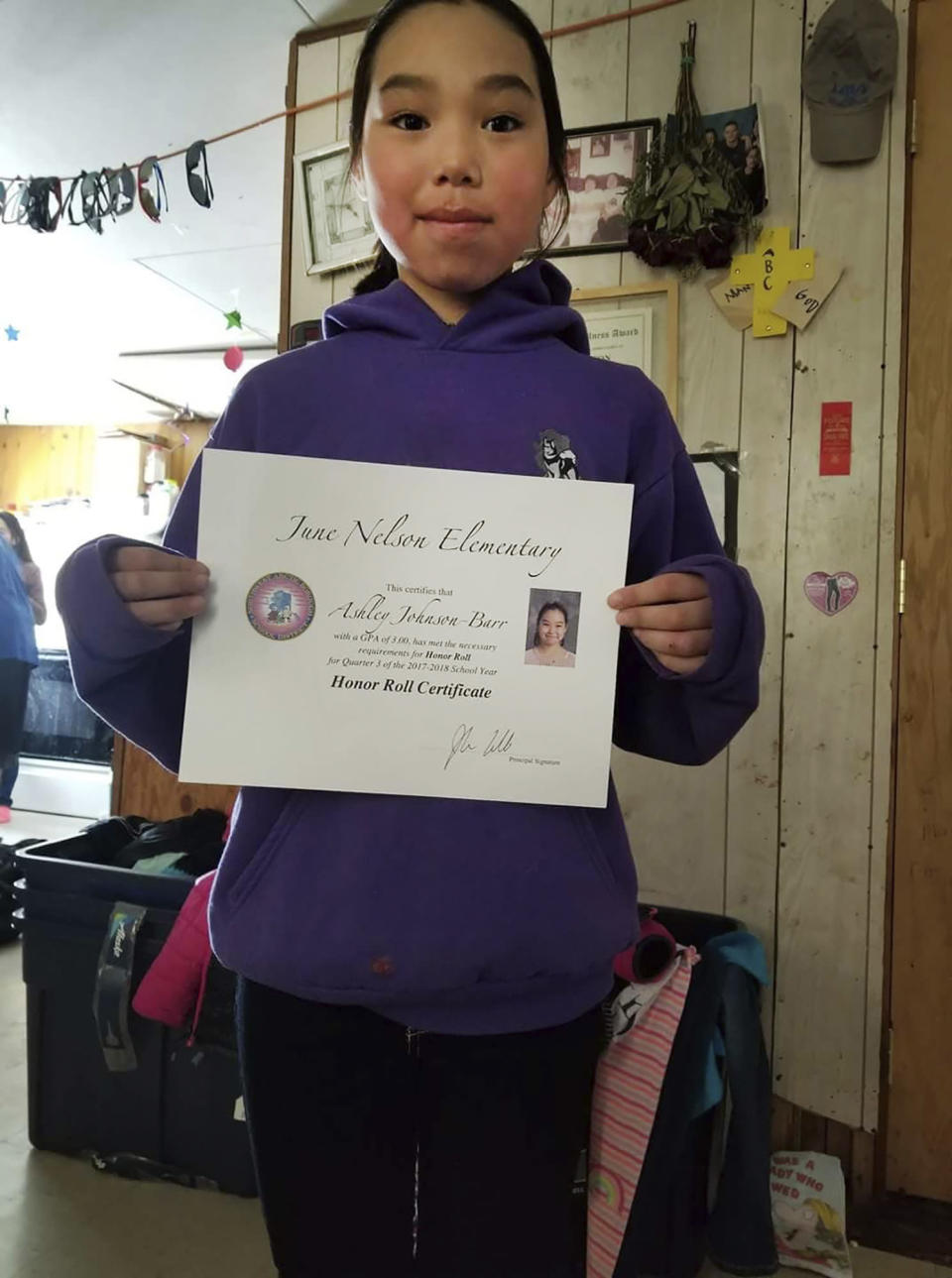 This 2018 photo provided by Scotty Barr shows his daughter Ashley Johnson Barr holding her Honor Roll certificate. Ashley was killed in Kotzebue, Alaska, in September 2018. Peter Wilson, of Kotzebue, Alaska, has pleaded guilty to first-degree murder and sexual abuse of a minor in Ashley's death, and will be sentenced Sept. 21, 2021, in Kotzebue. (Courtesy of Scotty Barr via AP)