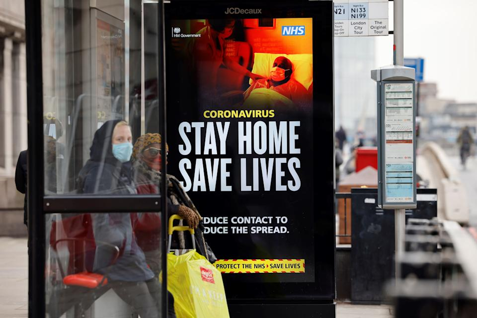 A woman wearing a face mask as a precautionary measure against COVID-19, waits in a busstop with NHS signage on keeping safe, at London Bridge in London on January 15, 2021, during the third coronavirus lockdown. - Britain's economy slumped 2.6 percent in November on coronavirus restrictions, official data showed January 15, 2021, stoking fears that the current virus lockdown could spark a double-dip recession. (Photo by Tolga Akmen / AFP) (Photo by TOLGA AKMEN/AFP via Getty Images)