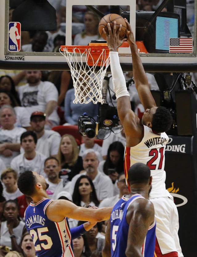 Miami Heat center Hassan Whiteside (21) dunks the ball in the second quarter over Philadelphia 76ers guard Ben Simmons (25) and center Amir Johnson (5) in Game 4 of a first-round NBA basketball playoff series, Saturday, April 21, 2018, in Miami. (AP Photo/Joe Skipper)