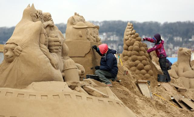 WESTON-SUPER-MARE, ENGLAND - MARCH 26: A sand sculptor works on a Toy Story themed sand sculpture as pieces are prepared as part of this year's Hollywood themed annual Weston-super-Mare Sand Sculpture festival on March 26, 2013 in Weston-Super-Mare, England. Due to open on Good Friday, currently twenty award winning sand sculptors from across the globe are working to create sand sculptures including Harry Potter, Marilyn Monroe and characters from the Star Wars films as part of the town's very own movie themed festival on the beach. (Photo by Matt Cardy/Getty Images)