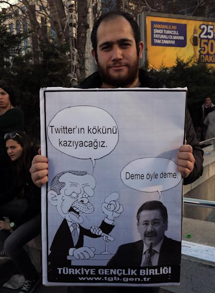 "A member of the Turkish Youth Union holds a cartoon depicting Turkey's Prime Minister Recep Tayyip Erdogan saying "" we will rip out the roots of Twitter"" and his Ankara Mayor Melih Gokcek replying ""don't say it"" during a protest against a ban on Twitter, in Ankara, Turkey, Friday, March 21, 2014. Turkey's attempt to block access to Twitter appeared to backfire on Friday with many tech-savvy users circumventing the ban and suspicions growing that the prime minister was using court orders to suppress corruption allegations against him and his government. (AP Photo/Burhan Ozbilici)"