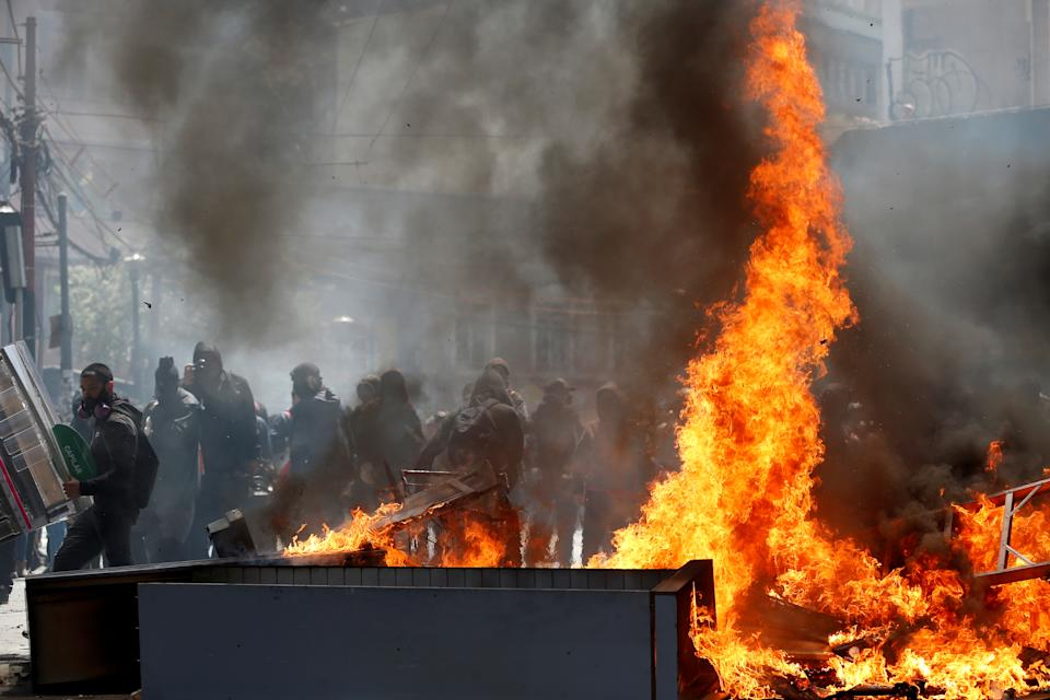 Demonstrators are seen behind a barricade on fire during clashes in Valparaiso, Chile on Oct. 23, 2019. (Photo: Rodrigo Garrido/Reuters)