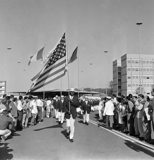 U.S. Flag bearer Rafer Johnson, from Kingsburt, Calif, carrying the United States flag as he leads Stars and Stripes the U.S. Olympic team out of the Olympic Village, to march to the Olympic Stadium for the opening ceremony of the Rome Summer Olympics, August 25, 1960. Rafer Johnson, world record holder in the Decathlon, and now a member of the U.S. track and field Olympic team, is the first black ever to be named to carry the American flag. (AP Photo/ Jim Pringle)