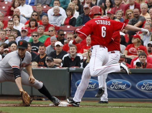 Cincinnati Reds' Drew Stubbs, right, safely reaches first base for a single in front of San Francisco Giants first baseman Brandon Belt, left, during the third inning of a baseball game, Thursday, April 26, 2012, in Cincinnati. (AP Photo/David Kohl)