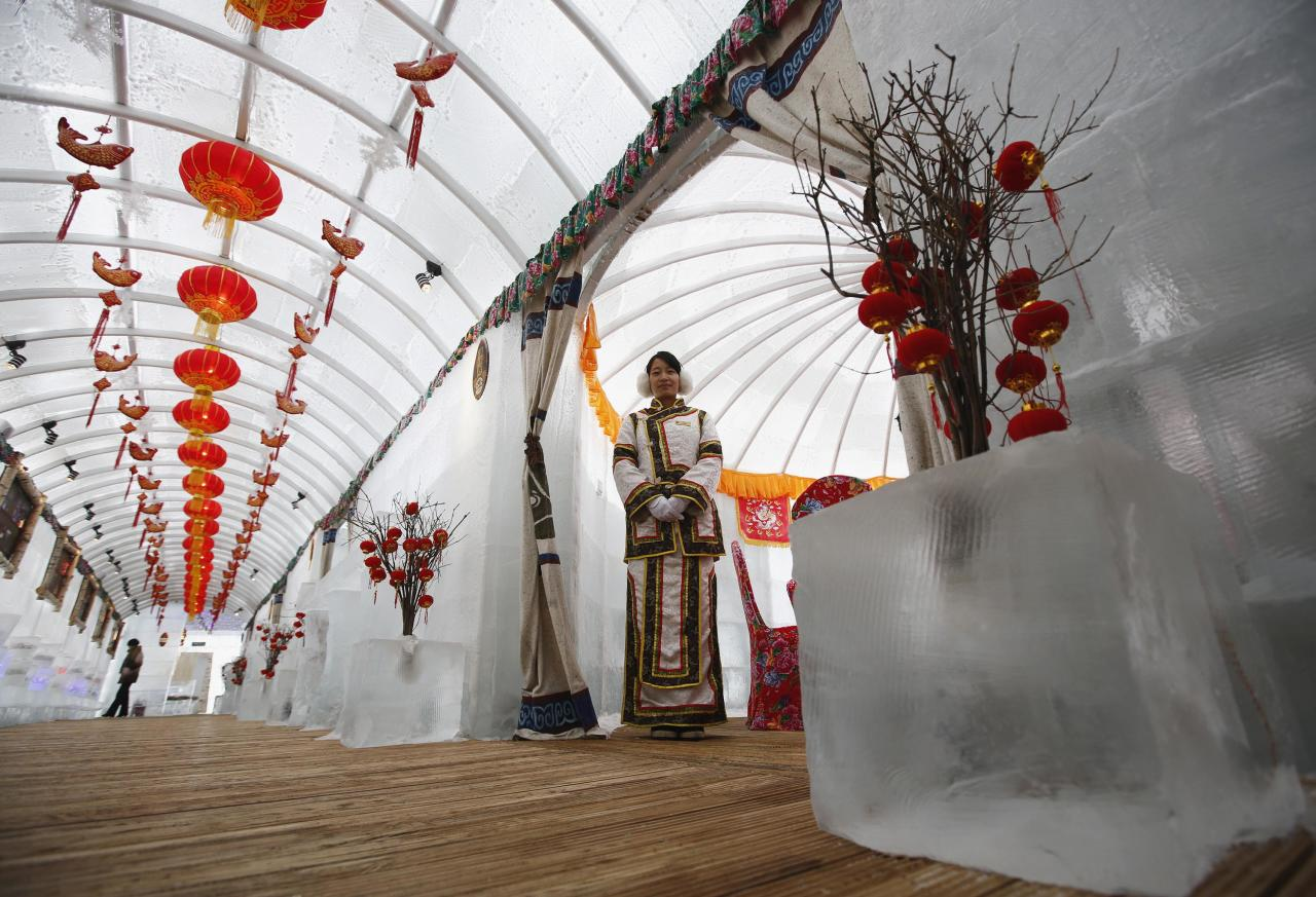 A waitress poses during a photo opportunity at the Ice Palace in Shangri-La Hotel in the northern city of Harbin, Heilongjiang province January 6, 2014. The Ice Palace, which is built by ice bricks, is open annually from December to February and attracts visitors during the Harbin Ice and Snow Festival. The temperatures inside the ice building is maintained around -10 degrees Celsius and it consists of bar and hot pot restaurant. REUTERS/Kim Kyung-Hoon (CHINA - Tags: SOCIETY TRAVEL ENVIRONMENT)