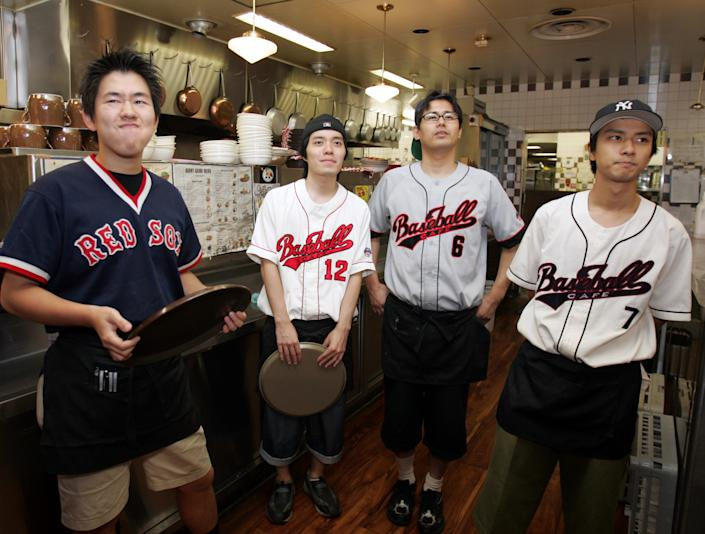 Employees at a baseball theme restaurant in Tokyo watch the television broadcast of Seattle Mariners outfielder Ichiro Suzuki's game in Oakland, California September 30, 2004. REUTERS/Yuriko Nakao