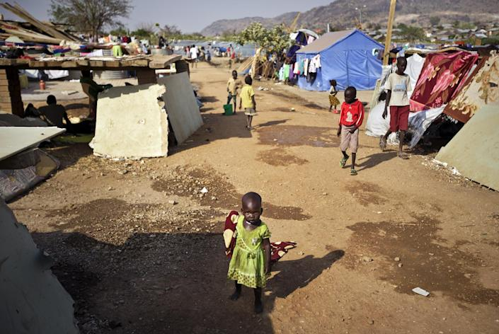 A young displaced girl drags a blanket along a path between makeshift shelters at a United Nations compound which has become home to thousands of people displaced by the recent fighting, in the Jebel area on the outskirts of Juba, South Sudan Tuesday, Dec. 31, 2013. Anti-government rebels took control of nearly all of the strategic city of Bor on Tuesday even as officials announced that representatives from the government and the rebels had agreed to hold talks for the first time. (AP Photo/Ben Curtis)