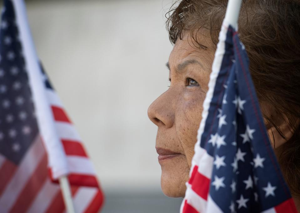 A woman holds a US flag as members of the November 2020 Coalition protest outside the Federal Building calling for the Trump administration to close border camps, free immigrant children and allow legal representation, in Los Angeles, September 16, 2019. (Photo by Mark RALSTON / AFP)        (Photo credit should read MARK RALSTON/AFP via Getty Images)