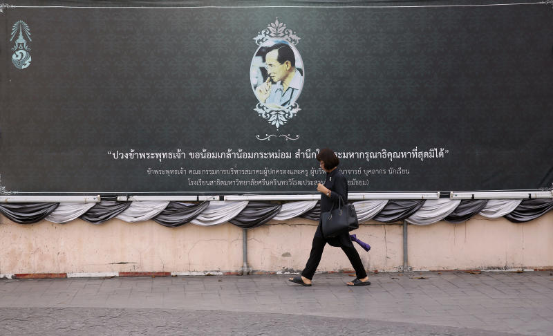 In this Oct. 10, 2017, photo, a woman dressed in black walks past a giant black toned memorial, edged with bunting, in honor of the late King of Thailand in Bangkok, Thailand. The muted colors of mourning have settled over Bangkok once again in recent weeks as the country marks a year since the death of its beloved monarch, King Bhumibol Adulyadej, and prepares for the national spectacle of his cremation next week. (AP Photo/Wally Santana)