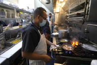 Jaime Hernandez cooks shrimp at Brenda's French Soul Food in San Francisco, Wednesday, Dec. 9, 2020. In pre-pandemic days, Brenda's French Soul Food was always hopping, but everything came to a screeching halt on March 16, when San Francisco halted indoor dining to stop the spread of the coronavirus. It reopened for takeout and delivery, and Chef Proprieter Brenda Buenviaje is now shipping meals nationwide through a service called Goldbelly. (AP Photo/Jeff Chiu)