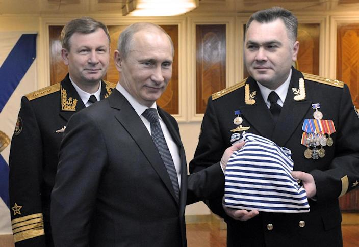 Russian President Vladimir Putin, center, receives a navy t-shirt as a gift, on board a navy ship in Severomorsk, Russia, on Thursday, Jan. 10, 2013. Russian Navy's commander-in-chief Viktor Chirkov is at left, and Vladislav Malakhovsky, captain of the Peter the Great nuclear powered cruiser is at right. (AP Photo/RIA Novosti, Alexei Nikolsky, Presidential Press Service)