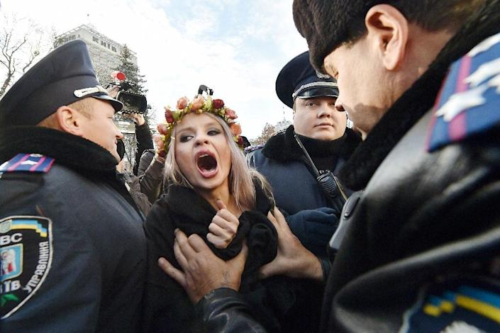 Ukrainian police detain an activist of the feminist movement Femen during a demonstration calling for gay rights outside the Ukrainian parliament in Kiev on November 12, 2015 (AFP Photo/Sergei Supinsky)