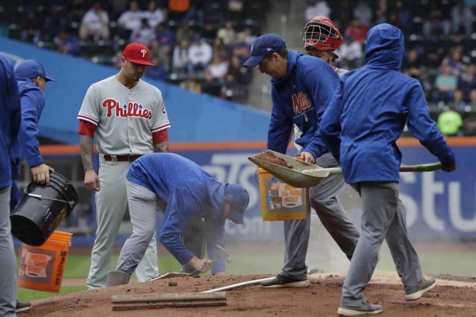 Philadelphia Phillies pitcher Vince Velasquez watches as the New York Mets grounds crew works on the pitcher's mound during a light rain in the first inning of a baseball game against the Mets, Sunday, Sept. 9, 2018, in New York. (AP Photo/Mark Lennihan)