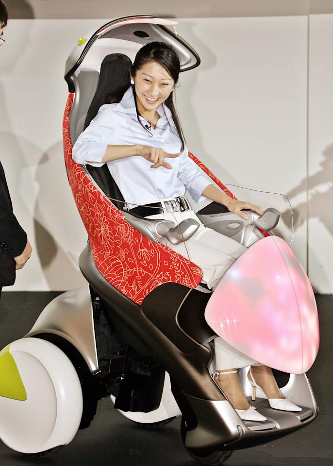 """A girl tries to ride a concept model of the one-seater three-wheel vehicle for the future city comuter """"i-swing"""" at the press preview of the 39th Tokyo Motor Show in Makuhari, suburban Tokyo 19 October 2005. Asia's largest motor show will open from 21 October.    AFP PHOTO / Yoshikazu TSUNO"""