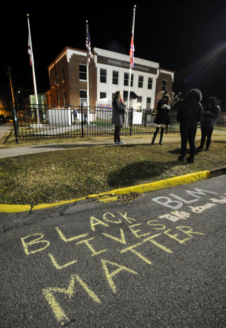 Demonstrators gather outside the Marshall County Courthouse in Albertville, Ala., on Wednesday, Dec. 9, 2020, following a protest against a Confederate monument and flag located on the lawn. Unique Morgan Dunston, a Black woman transformed by leaving the virtually all-white town where she grew up, has been leading the demonstrations since August. (AP Photo/Jay Reeves)