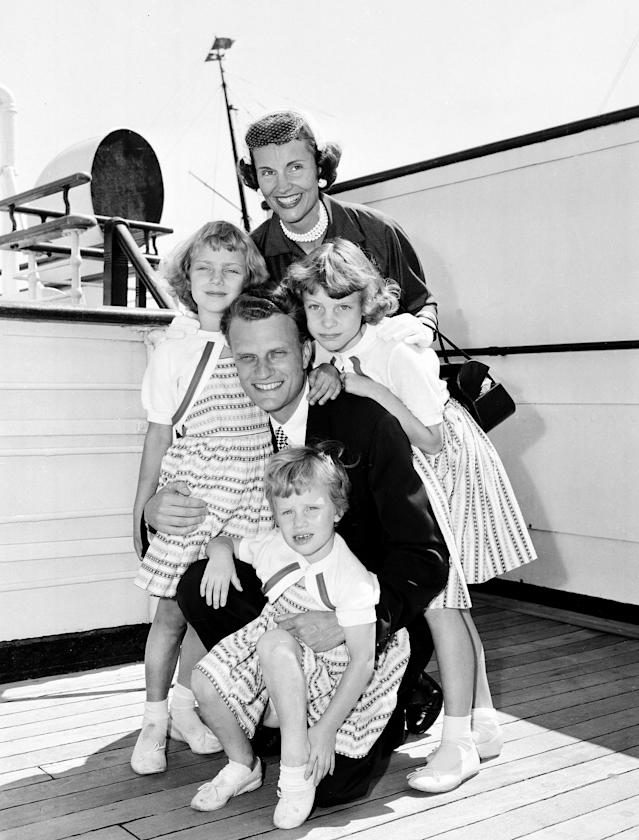 <p>Billy Graham poses with his his wife, Ruth, and their three daughters on the Queen Mary after arriving in New York, July 7, 1954. (Photo: AP) </p>