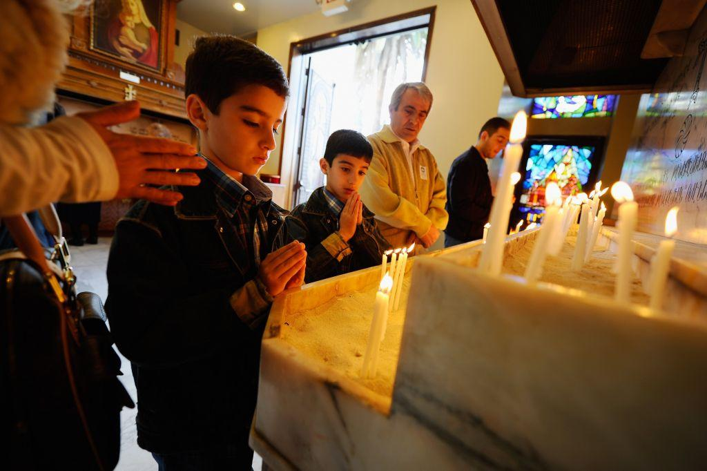 LOS ANGELES, CA: Armenian children pray after lighting candles at St. Garabed Armenian Apostolic Church during Christmas mass. File photo: January 6, 2011