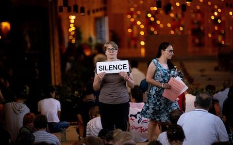 A worshipper holds a sign reminding attendees to be quiet during morning prayers in Taizé - Credit: Charlotte Graham/Charlotte Graham