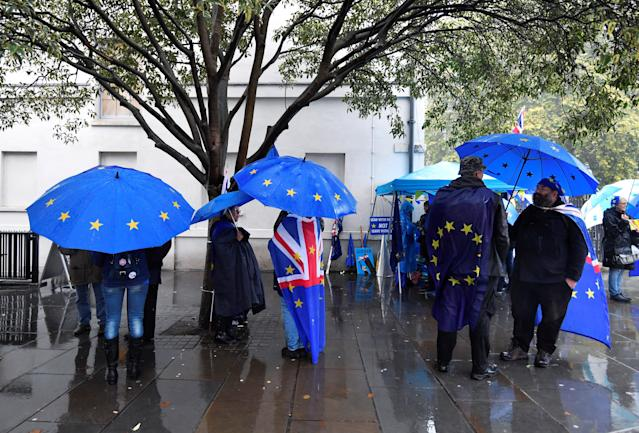 Anti-brexit and pro-EU protesters shelter from the rain outside the Houses of Parliament in London. Photo: Toby Melville/Reuters