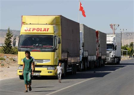 Locals walk past trucks lined up at the Oncupinar border crossing on the Turkish-Syrian border in Kilis