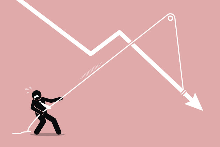 A stick figure businessman trying to pull a falling chart higher with a pulley system.
