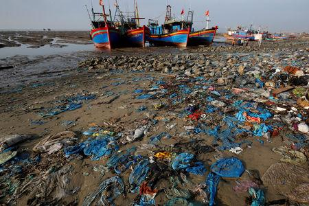 FILE PHOTO: Fishing boats are seen at a beach covered with plastic waste in Thanh Hoa province, Vietnam June 4, 2018. REUTERS/Nguyen Huy Kham