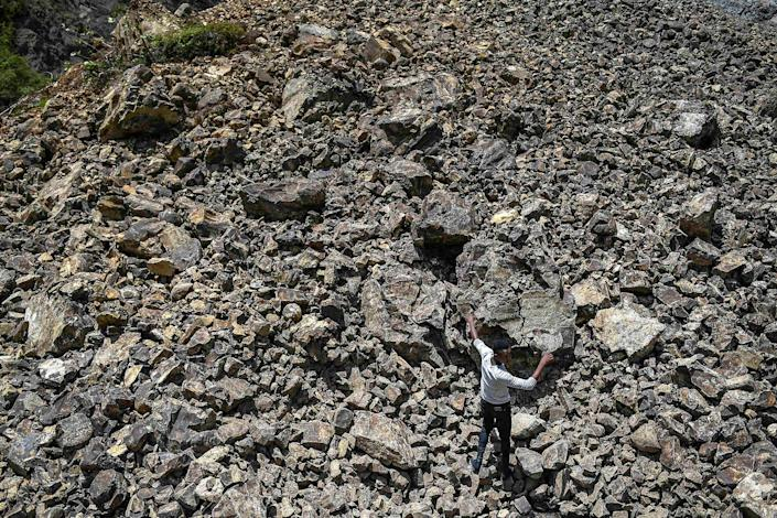 """A man walks over rubble that covered a road during a landslide triggered by the earthquake in River Glass on Aug. 18.<span class=""""copyright"""">Matias Delacroix—AP</span>"""