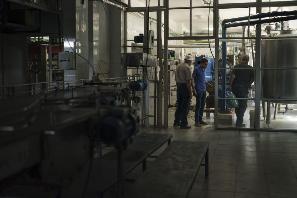 Palestinian employees work at the Pepsi bottling plant in Gaza City, Monday, June 21, 2021. Israel on Monday eased some restrictions on the Gaza Strip however the Pepsi factory announced today that it was closing and laying off workers because raw materials needed to stay in business are still not coming. (AP Photo/Felipe Dana)