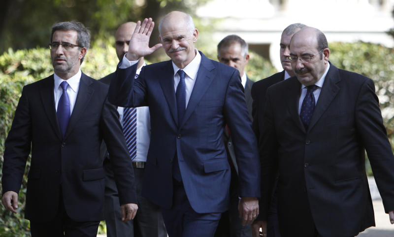 Outgoing Prime Minister George Papandreou waves to the media as he leaves the presidential palace in Athens, Thursday, Nov. 10, 2011. Lucas Papademos was named Thursday as the prime minister of the new Greek interim government, charged with keeping the debt-strapped country out of bankruptcy and firmly in the 17-nation eurozone. After four days of intense political negotiations, the 64-year-old former vice president of the European Central Bank was chosen to lead a coalition backed by both the governing Socialists and opposition conservatives that will operate until early elections in February. (AP Photo/Thanassis Stavrakis)