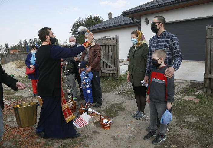 Priest of Ukrainian Orthodox Church Nazariy, wearing a face mask to protect against coronavirus, blesses family members near their house in the village of Nove close to capital Kyiv, Ukraine, Saturday, April, 18, 2020. All the Ukrainian churches have been closed for people because of COVID-19 outbreak, and believers wait for the priest near their houses. For Orthodox Christians, this is normally a time of reflection, communal mourning and joyful release, of centuries-old ceremonies steeped in symbolism and tradition. But this year, Easter - by far the most significant religious holiday for the world's roughly 300 million Orthodox - has essentially been cancelled. (AP Photo/Efrem Lukatsky)