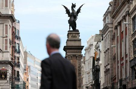 FILE PHOTO: A pedestrian walks past a City of London dragon boundary marker in London, Britain,  September 23, 2015. REUTERS/Suzanne Plunkett/File Photo