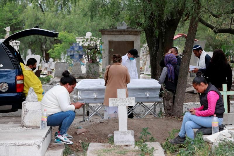 A funeral worker looks at a family saying their last goodbyes to their relative who died of the coronavirus disease (COVID-19) at the San Lorenzo Tezonco cemetery in Mexico City