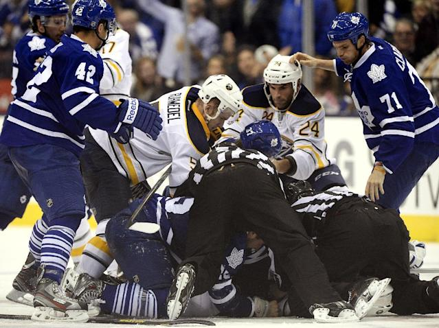 Buffalo Sabres and Toronto Maple Leafs pile-up during the third period of an NHL hockey preseason hockey game in Toronto, Sunday, Sept. 22, 2013. (AP Photo/The Canadian Press, Frank Gunn)