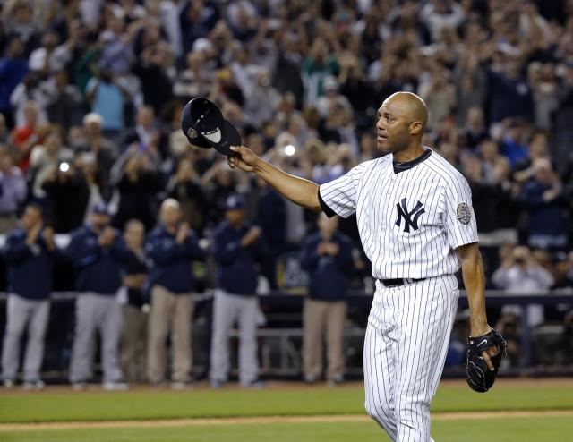 New York Yankees relief pitcher Mariano Rivera tips his cap to the crowd and the Tampa Bay Rays (rear) as they applaud him as he leaves the game in the ninth inning of their MLB American League game at Yankee Stadium in New York, September 26, 2013. It was Rivera's final appearance at the Stadium as he is retiring at the end of the season. REUTERS/Ray Stubblebine (UNITED STATES - Tags: SPORT BASEBALL)