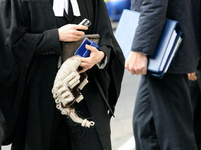 A barrister carries a wig