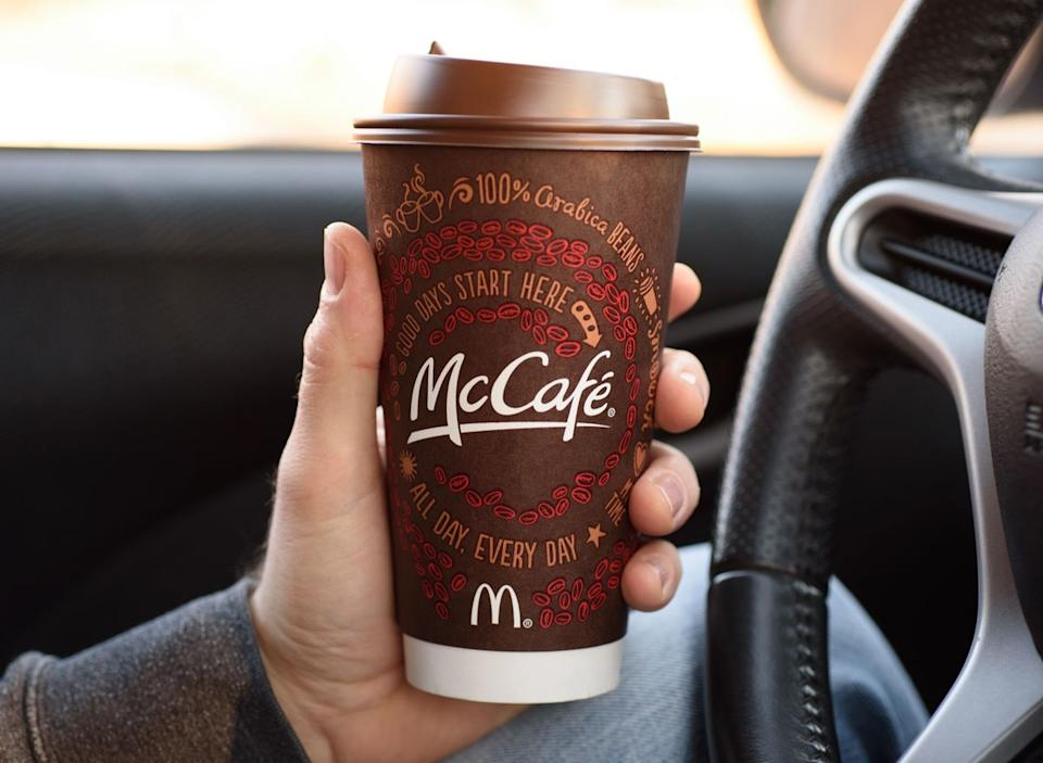 Man holding mccafe coffee cup from mcdonalds in car